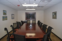 A board room with a long table in the middle with black chairs and a tv onthe wall