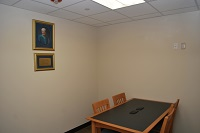 A small stufy room with a photo on the wall and 1 table with 4 chairs